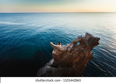 Kundalini yoga on a cliff above the blue sea at sunset. Young beautiful woman in white with a perfect figure back.