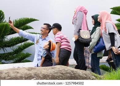 Kundasang Sabah Malaysia - Dec 17, 2016 : Unidentified family taking selfie using handphone at Kudasang Sabah.Kundasang a highland in Borneo is popular destination among tourist.
