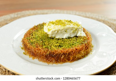 Kunefe, Kunafa, Kutayfa, Traditional Turkish Dessert with Kaymak or ice cream, white plate with wooden background, Künefe