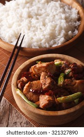 Kung pao chicken fillets in a bowl close up and rice. vertical