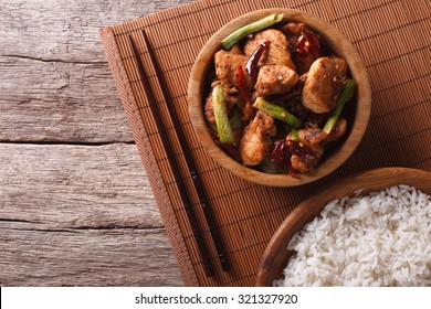 Kung pao chicken fillets in a bowl and rice. horizontal view from above