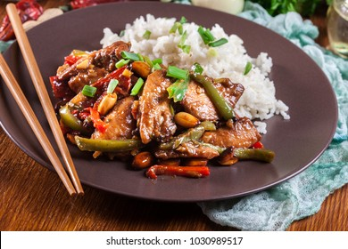 Kung Pao chicken with peppers and vegetables served with rice. Traditional sichuan dish