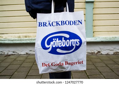 Kungalv / Sweden - Nov 22 2018: A man carrying a white paper bag with the symbol and text for the famous Swedish bakery company Goteborgs Kex.