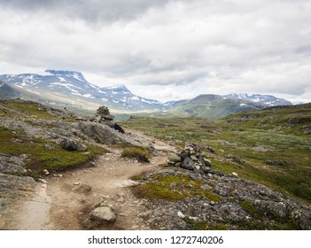 Kungsleden hiking trail winding through rocky mountain landscape, Lapland Sweden. Snowy mountains in the background and cairn marking trail in the foreground.