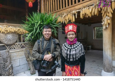 KUNMING, CHINA-MARCH,15, 2019:A young man take picture with a lady Dressed In Ancient National Costume in Yunnan Nationalities Village, Kunming City, Yunnan Province, China.