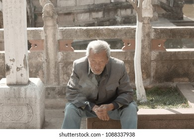 Kunming, Yunnan, China - 28 December 2017: An old man is smoking in the Yuantong Temple