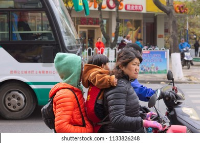 Kunming, Yunnan, China - 30 December 2017: A chinese family on the scooter