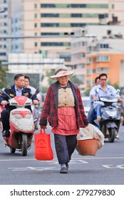 KUNMING-JUNE 30, 2014. Elder woman carries bag and bucket with stuff on the road. China's elderly population (60 or older) is about 128 million, one in every ten people, the largest in the world.