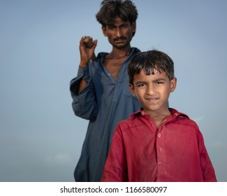 Kunri, Sindh/Pakistan - Aug 28, 2018: Boy Standing in front of his father