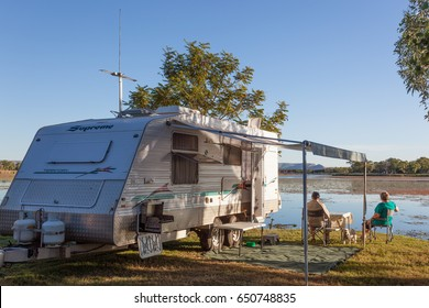 KUNUNURRA, AUSTRALIA - JUL 7, 2013: Retired Australians known as Grey Nomads emerge from their caravans and enjoy afternoon drinks and sunset on the bank of Lake Kununurra during the annual Dry Season
