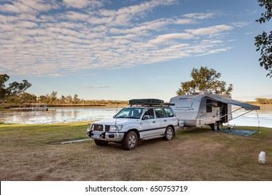 KUNUNURRA, AUSTRALIA -  JUL 7, 2013: A Four wheel drive vehicle and offroad caravan on the banks of Lake Kununurra. Typical of the hundreds that frequent the area each year in the cooler dry season.