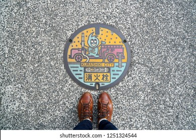 Kurashiki City,Japan - 4 Dec 2018:Beautiful graphic manhole cover on the floor at Japan,Picture focus on Steel Manhole cover for drainage with shoes leather.Unique and create.