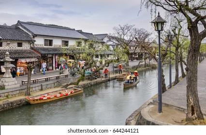 KURASHIKI,  JAPAN - APRIL 07, 2017 : Unknown tourists  are enjoying with the old-fashioned boat along the Kurashiki canal in Bikan district of  Kurashiki city, Japan.