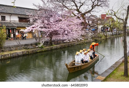 KURASHIKI, JAPAN - APRIL 07, 2017 : Unknown tourists are enjoying  the old-fashioned boat along the Kurashiki canal in Bikan district of Kurashiki city, Japan.