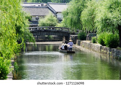 Kurashiki, Japan - June 5, 2012: Tourists enjoy boat ride in old Japanese town, Kurashiki in Japan