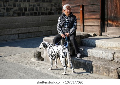 KURASHIKI, JAPAN - MARCH 31, 2019: Japanese man with a dog breed Dalmatian resting on the steps near the house in Kurashiki city, Japan.