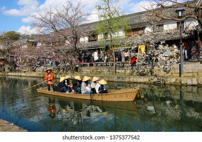 KURASHIKI, JAPAN - MARCH 31, 2019: Tourists are enjoying the old-fashioned boat along the Kurashiki canal in Bikan district of Kurashiki city, Japan.