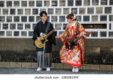 KURASHIKI, JAPAN - MARCH 31, 2019: Young man and a girl in kimono dress imitate playing on electric guitars against the background of a traditional wall of a house in Kurashiki city, Japan.