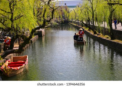 KURASHIKI, JAPAN - MARCH 31, 2019: Tourists are enjoying the old-fashioned boat along the Kurashiki canal