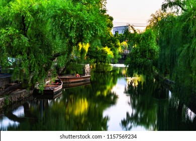 Kurashiki, Japan. View of famous canal in Kurashiki, Japan in the evening. Two old wooden boats moored, motion blurred river with green trees