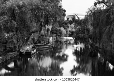 Kurashiki, Japan. View of famous canal in Kurashiki, Japan in the evening. Two old wooden boats moored, motion blurred river with green trees. Black and white