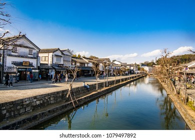 KURASHIKI, OKAYAMA, JAPAN - FEB 17, 2018: Canals of Kurashiki Bikan Historical Quarter with shops at the river bank in white traditional houses in Okayama, Japan.