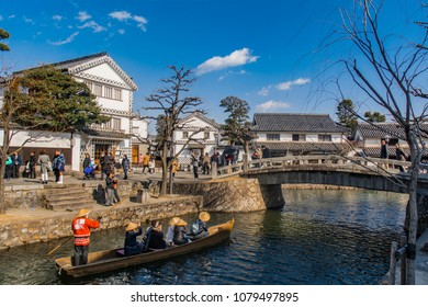 KURASHIKI, OKAYAMA, JAPAN - FEB 17, 2018: Old-fashioned cruise boats with tourists smiling in the Canals of Kurashiki Bikan Historical Quarter in Okayama, Japan.