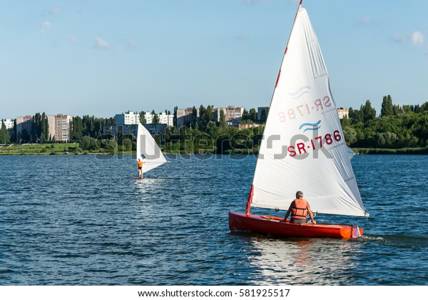 KURCHATOW, RUSSIA - JUNE 23, 2016: Man on sailing boat and windsurfer train on the lake.