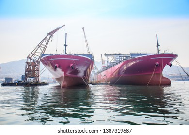 KURE, JAPAN - APRIL 7, 2019: Two giant purple cargo ships are being loaded with shipping containers in the famous shipping yard in Kure.
