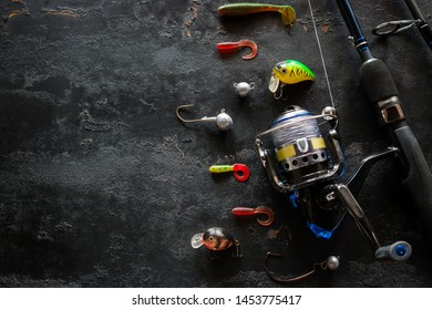 Kurgan, Russia, June 10, 2019 fishing rod spinning and various bait for fishing on a black background with space for text