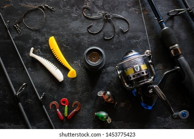 Kurgan, Russia, June 10, 2019 fishing rod spinning and bait for fishing on a black background with space for text