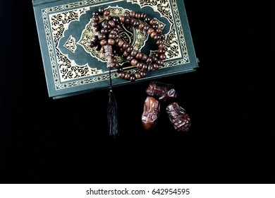 Kurma or Dried Dates Popular During Ramadhan or Fasting Month, Holy Quran and rosary or tasbih with black background.