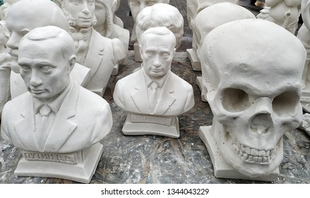 KURSK, RUSSIA - MARCH 17, 2019: Gypsum figures on the street market: the skull and bust of Russian President Vladimir Putin