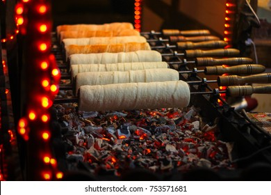 Kurtos kalacs (Chimney Cakes) baking on roll spinning over hot coals at a Christmas market stand
