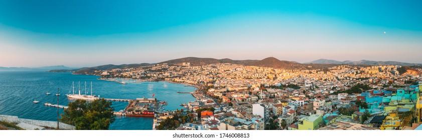 Kusadasi, Aydin, Aydın Province, Turkey. Waterfront And Kusadasi Cityscape In Sunny Summer Evening. Scenic View Of Kusadasi Skyline At Aegean Coast, Turkey. Panorama, Panoramic View.