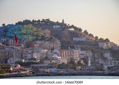 "Kusadasi, Turkey - 07.26.2019 The city of Kusadasi in Turkey and the letters above it saying ""Kusadasi""."