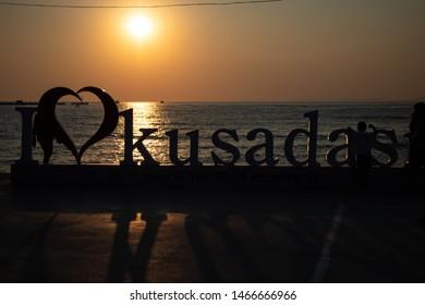 "Kusadasi, Turkey - 07.26.2019 Letters in the center of Kusadasi, Turkey saying ""I love Kusadasi"" with a beautiful sunset behind them."