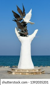 KUSADASI, TURKEY - APRIL, 2019 : The hand of peace sculpture with doves on the waterfront in Kusadasi, Turkey