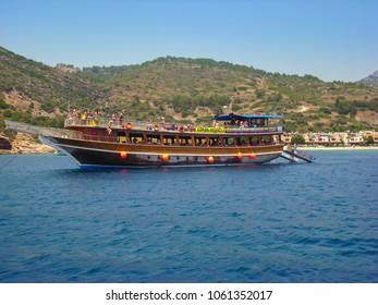 Kusadasi, Turkey - June 17 2012 : tourist having fun on an small cruise boat anchored near the beach.