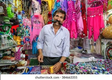 KUSADASI, TURKEY - JUNE 2, 2013: Unidentified turkish seller with big mustache works in his souvenir shop in Kusadasi, Turkey