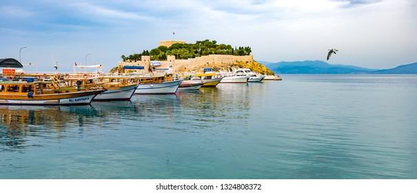 Kusadasi, Turkey - June 2, 2014: A panoramic view of boats, birds, and Pigeon Island in Kusadasi.