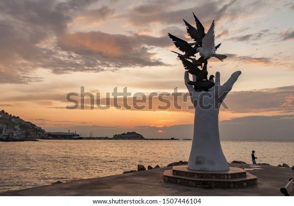 Kusadasi, Turkey - September 17, 2019: The hand of peace sculpture with doves on the waterfront in Kusadasi, Turkey.  Hand feeding birds. Sunset on the beach.