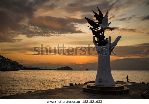 Kusadasi, Turkey - September 17, 2019: The hand of peace sculpture with doves on the waterfront in Kusadasi, Turkey.