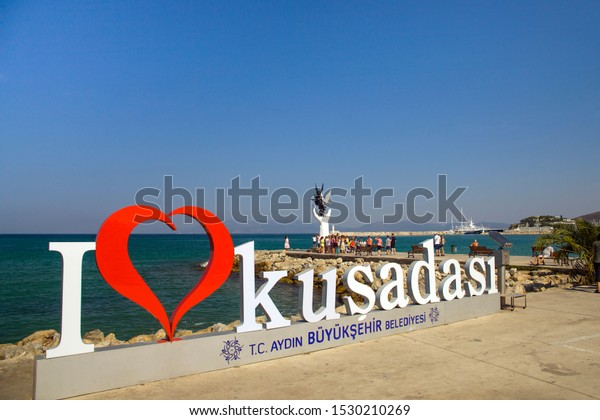 Kusadasi, Turkey - September 17, 2019: The marina in Kusadasi. The coast and port in the city, fishing boats and tourist ship. Place of holiday photos.