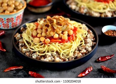 Kushari or Koushari - Egyptian dish of lentils, rice, pasta, chickpeas with tomato sauce and crispy onions. Arabic cuisine
