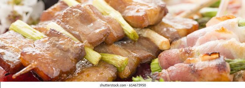 Kushiyaki - Butabara (belly pork) and Asuparabekon (asparagus wrapped in bacon). Japanese grilled food on skewers.