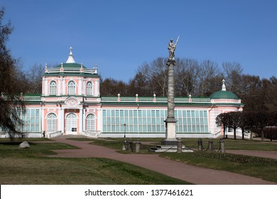 Kuskovo manor, Moscow - APRIL 17, 2019: View on a sunny day to the Large Stone Orangery in the neoclassical style and  an obelisk with a statue of a female warrior with a bronze spear in front of it