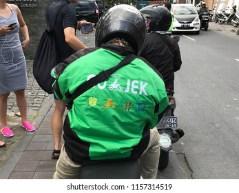 Kuta, Bali, Indonesia - August 16, 2018: Backside of a unidentifiable Go-jek motor taxi driver standing boy the side of the road. Gojek is a Indonesian transportation startup.