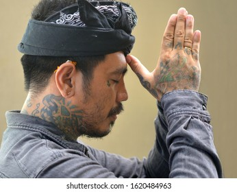 KUTA, BALI / INDONESIA - JAN 10, 2020: Young Balinese man with tattoos on his neck and the back of his hand wears a traditional udeng head wear and prays to the Hindu gods, on Jan 10, 2020.