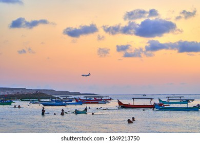 KUTA, BALI ISLAND, INDONESIA - SEPTEMBER 9, 2018: Landing plane in the background of famous Kuta Beach. Traditional Balinese boats and swimmers under at the sunset time.